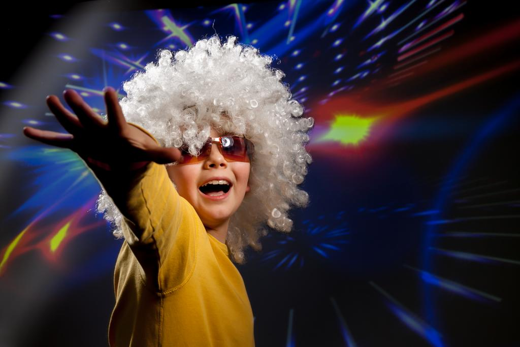 Canva - Child in glasses and a wig dances in disco lights.jpg
